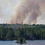 A dark smoke plume is visible above the forested island, lake in the foreground.