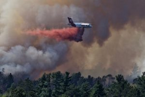 Heavy aircraft flying in dark smoke and dropping red retardant over the forest.