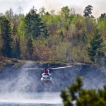 A helicopter drawing water from a lake surrounded by forest.