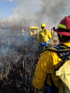 Firefighters and equipment fight wildfire